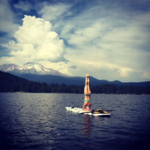 emilee doing a handstand on a paddle board on a lake